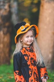 Menina fantasiada de bruxa fica no parque no outono, no feriado de halloween.