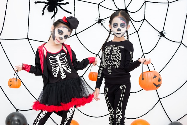 Menina fantasiada de carnaval de halloween está segurando a lanterna de jack