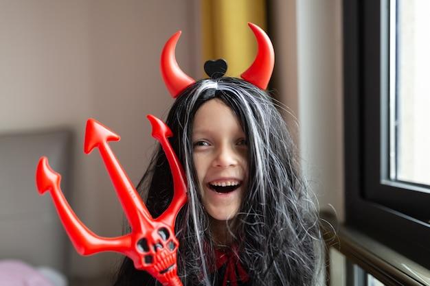 Menina fantasiada de demônio com chifres vermelhos em casa