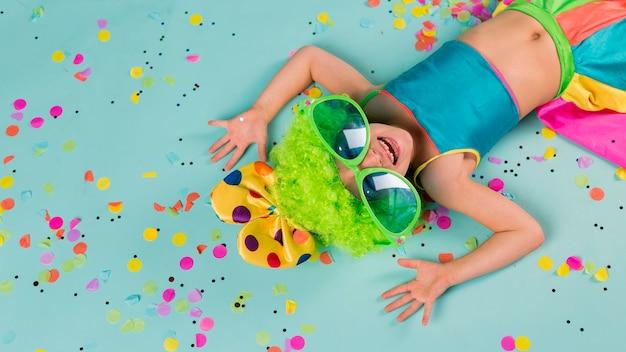 Menina fantasiada de palhaço com confete e óculos escuros