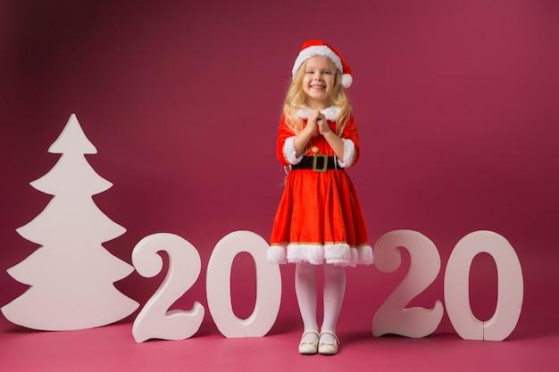 Menina fantasiada de papai noel fica com números 2020