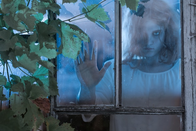 Menina fantasma na janela antiga
