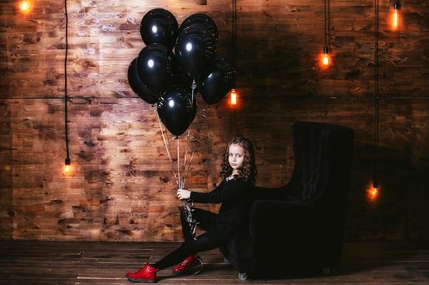 Menina fashion com um monte de balões pretos contra a parede com lâmpadas