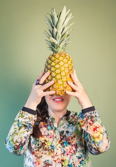 Menina fashion segurando abacaxi na frente do rosto
