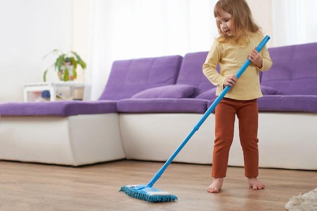 Menina faz a limpeza no quarto. diversão infantil, limpando o esfregão de chão