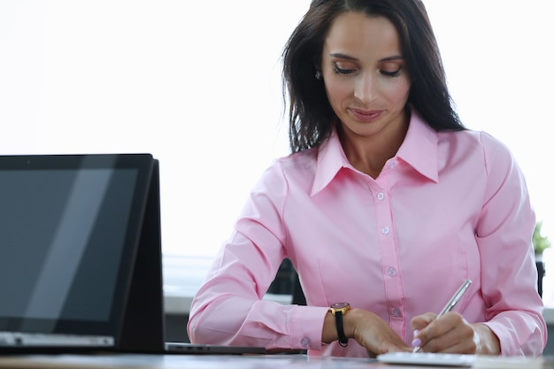 Menina faz anotações com caneta, na mesa no escritório