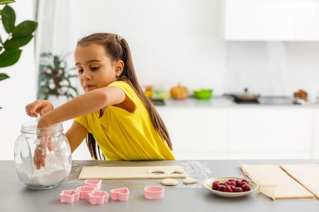 Menina faz biscoitos da massa na cozinha em casa