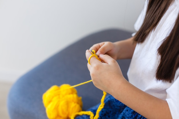 Menina faz crochê com fios amarelos. vista do topo. fazendo decoração.