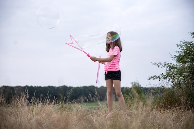 Menina faz grandes bolhas de sabão multicoloridas na natureza, no campo, atividades ao ar livre no verão.