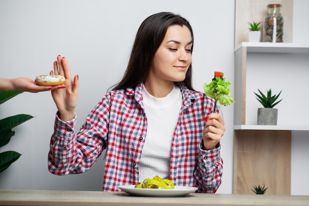 Menina faz uma escolha entre alimentos saudáveis e prejudiciais