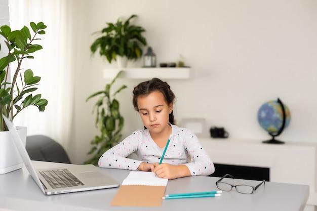 Menina fazendo a lição de casa em casa e usando um laptop