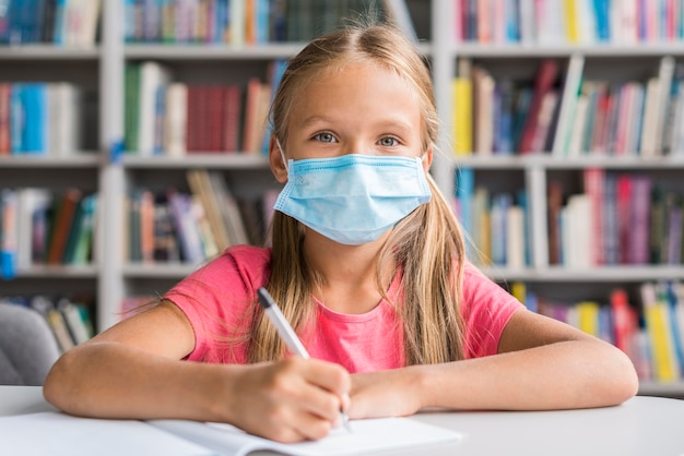 Menina fazendo a lição de casa enquanto usava uma máscara médica