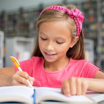 Menina fazendo a lição de casa na biblioteca