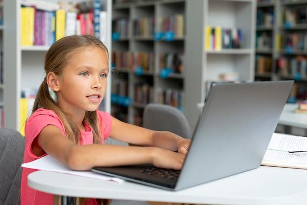 Menina fazendo a lição de casa no laptop da biblioteca
