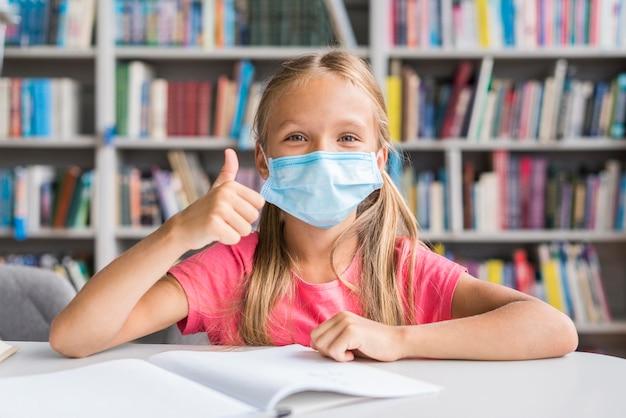 Menina fazendo a lição de casa usando uma máscara facial