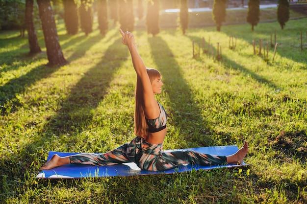 Menina, fazendo, asana, hanumanasana, com, mãos, cima, gramado, em, a, parque, em, sunlights