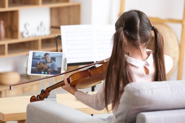 Menina fazendo aulas de música online em casa