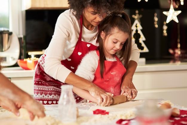 Menina fazendo biscoitos com a mãe