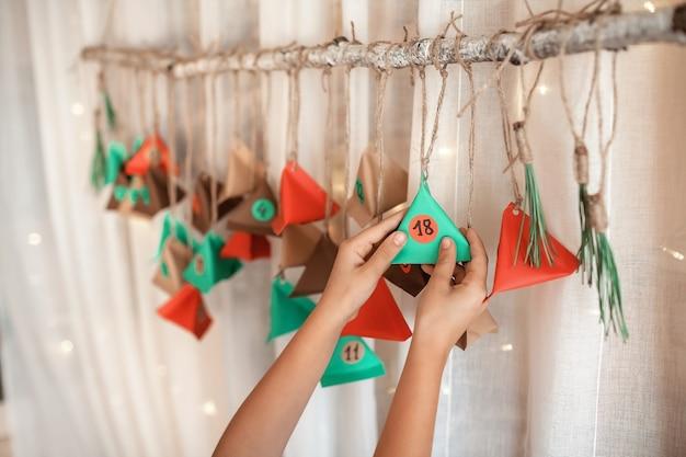 Menina fazendo calendário de natal do advento feito à mão com triângulos de papel colorido