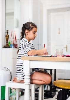 Menina fazendo desenhos em um livro enquanto está sentada à mesa em casa