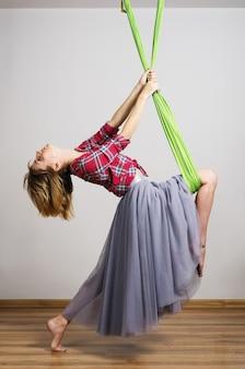 Menina fazendo exercícios com rede para ioga