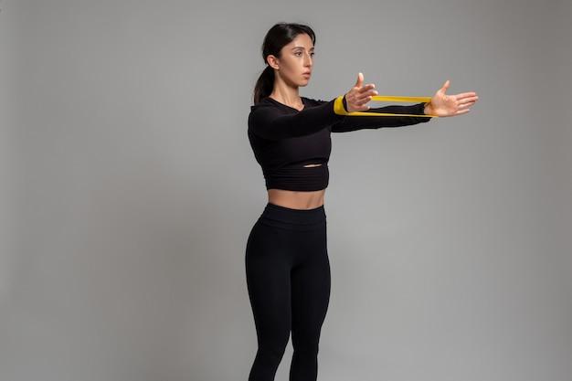 Menina fazendo exercícios de braço e ombro com faixa de resistência na parede cinza