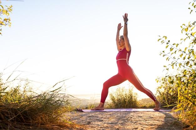 Menina fazendo exercícios de ioga com as duas mãos para cima em um tapete esportivo ao nascer do sol