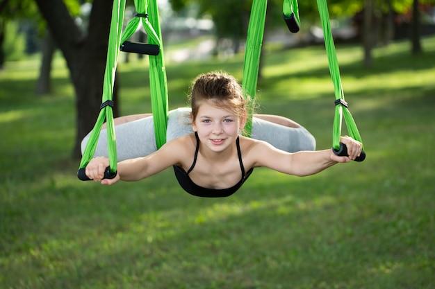 Menina fazendo exercícios de ioga com uma rede no parque