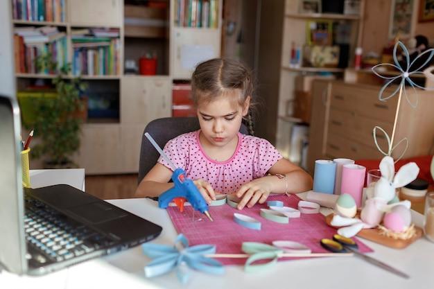 Menina fazendo flores com tubo de rolo de papel higiênico via master class online, zero desperdício de páscoa e dia das mães