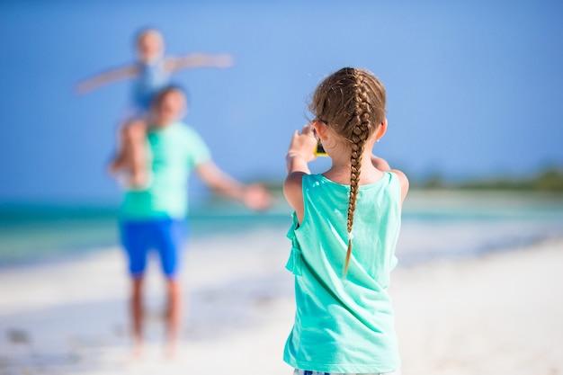 Menina fazendo foto no telefone da família na praia
