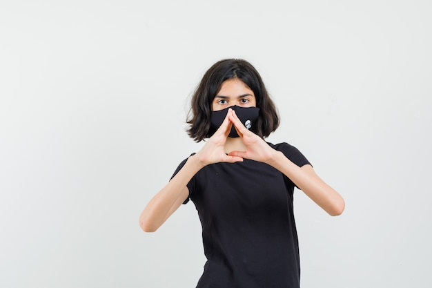 Menina fazendo gesto de coração em t-shirt preta, máscara e olhando confiante, vista frontal.