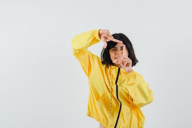 Menina fazendo gesto de quadro com capuz amarelo e olhando alegre, vista frontal.