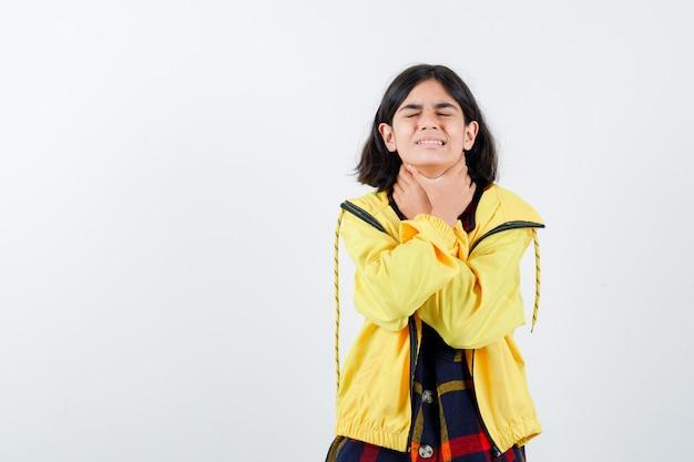 Menina fazendo gesto de suicídio com as mãos em uma camisa xadrez, jaqueta e parecendo infeliz