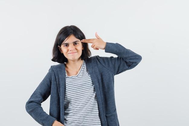 Menina fazendo gesto de suicídio em t-shirt, jaqueta e parecendo confiante.