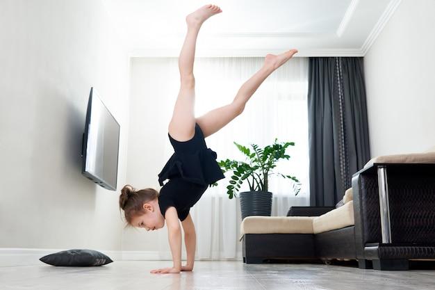 Menina fazendo ginástica em casa em pé nas mãos de cabeça para baixo