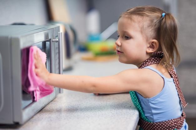 Menina fazendo limpeza na cozinha de casa