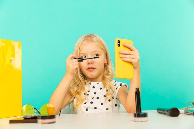 Menina fazendo maquiagem na câmera para o vlog. trabalho como blogger, gravando vídeo tutorial para internet.