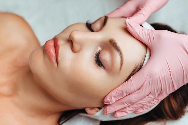 Menina fazendo massagem facial na esteticista no salão spa