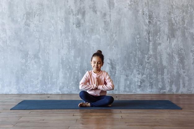 Menina fazendo meditação de ioga sentada no tapete