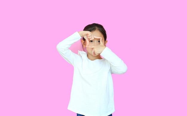 Menina fazendo moldura com as mãos e dedos em fundo rosa