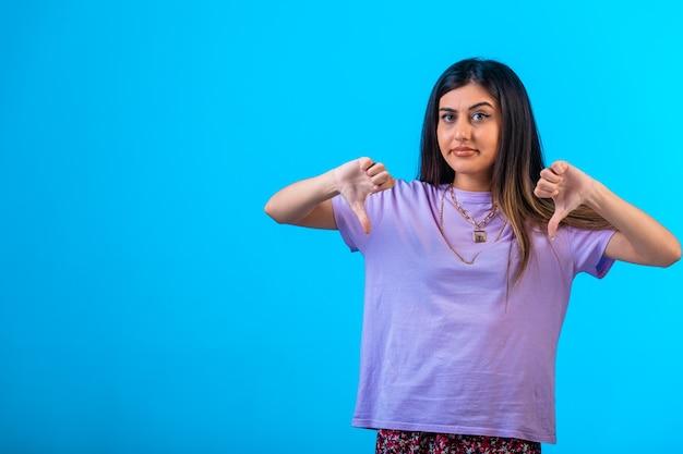 Menina fazendo sinal de polegar para baixo com as duas mãos