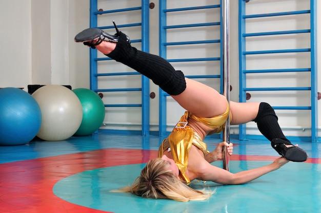 Menina fazendo um elemento de pole dance