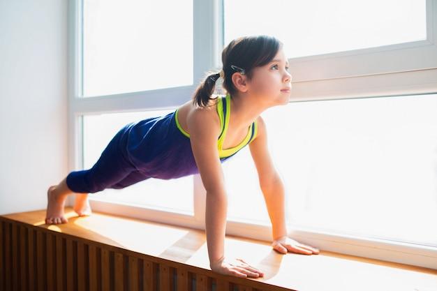 Menina fazendo um exercício de prancha exercício em casa. garoto bonito está treinando em um peitoril da janela de madeira interior. pequena modelo feminina de cabelos escuros no sportswear tem exercícios perto da janela no quarto dela.