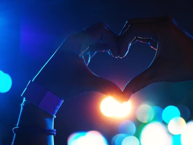 Menina fazendo um símbolo em forma de coração em concerto.