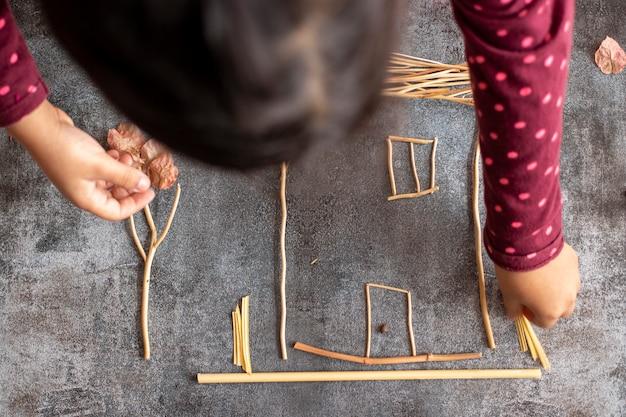 Menina fazendo uma casa com raminhos de plantas