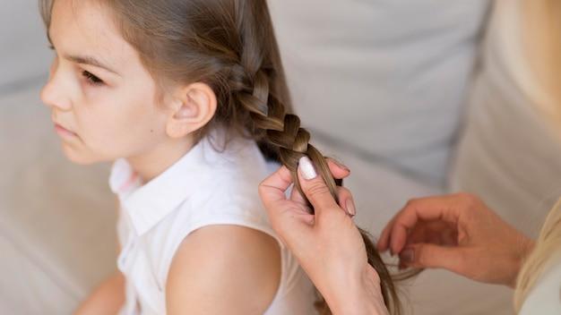 Menina fazendo uma trança no cabelo pela mãe em casa