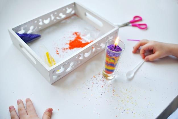 Menina fazendo uma vela com pequenos grânulos de parafina