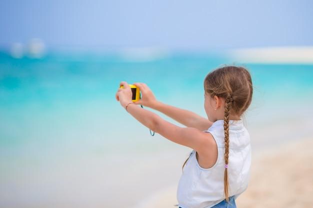 Menina fazendo vídeo ou foto de praia tropical com a câmera para a memória