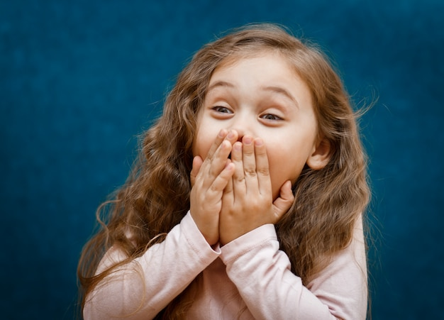 Menina fecha a boca com as mãos emoções