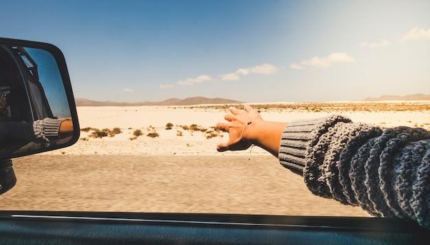 Menina fecha a mão brincando com o vento como uma asa do lado de fora do carro, viajando para férias alternativas com vista para o deserto e montanhas
